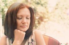 Женщина daydreaming в мирном саде Стоковые Изображения