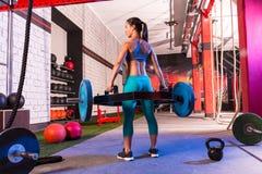 Женщина Deadlifts бара пожимания плечами подъема наговора мертвая на спортзале Стоковые Фото