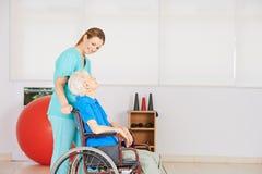 Женщина dring попечителя старшая в кресло-коляске Стоковые Фото