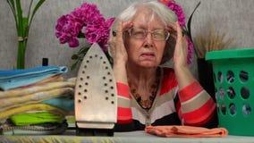 Женщина Ederly с доской головных болей близко утюжа видеоматериал