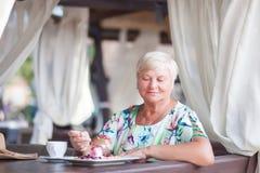 Женщина eldery сидя в доме coffe Стоковое Изображение RF