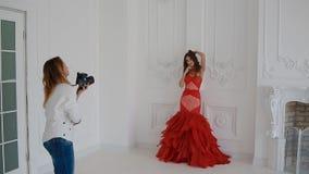 Женщина Gergeous в красном платье представляя в студии видеоматериал
