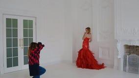 Женщина Gergeous в красном платье представляя в студии акции видеоматериалы