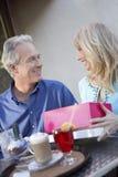 Женщина Gifting человека на таблице кафа Стоковые Изображения