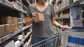 Женщина Handheld съемки азиатская красивая выбирает продукты в супермаркете С корзиной видеоматериал