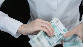 Женщина hesitantly подсчитывает деньги и стога счетов в одно изображение, русских рублей сток-видео