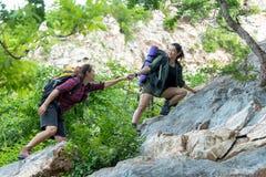Женщина Hiker группы помогая ее другу взбирается вверх последний раздел захода солнца в горах Сыгранность путешественника идя в в Стоковое Изображение RF