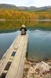 Женщина Hiker сидя над озером в осеннем дне Стоковое Фото