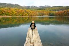 Женщина Hiker сидя над озером в осеннем дне Стоковые Изображения RF
