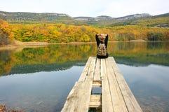 Женщина Hiker сидя над озером в осеннем дне Стоковое Изображение
