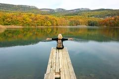 Женщина Hiker сидя над озером в осеннем дне Стоковое Изображение RF