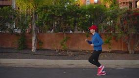 Женщина jogging вдоль улицы среди тропического переулка видеоматериал