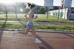 Женщина jogging на раннем утре Стоковая Фотография