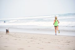 Женщина Jogs вниз с пляжа с ее собакой Стоковые Фото