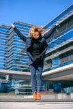 Женщина junping при руки вверх и строить сделанный из стекла Стоковые Фотографии RF