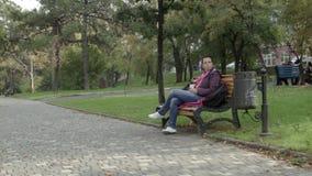 женщина 4K держит кофе и смотрит с оценкой в парке на стенде акции видеоматериалы