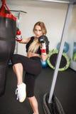 Женщина Kickboxer пробивая в тяжелую сумку Стоковая Фотография