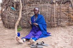 Женщина Masai делает ее handmade сувениры для продавать во времени которому туристы идут к Стоковые Изображения