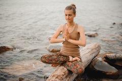 Женщина Meditating на пляже отступление йоги namaste в представлении лотоса Стоковое Изображение RF