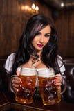 Женщина Oktoberfest нося традиционный баварский dirndl платья представляя с кружками пива на баре Стоковые Фото