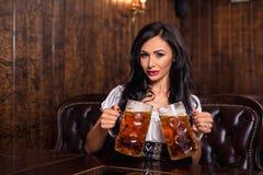 Женщина Oktoberfest нося традиционный баварский dirndl платья представляя с кружками пива на баре Стоковое фото RF