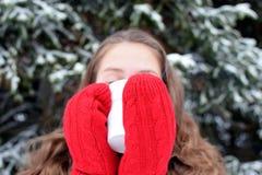 Женщина Oung с красными mittens выпивая горячие чай или кофе в зиме Стоковые Фото