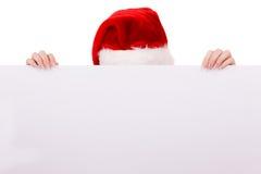 Женщина peeking над пустой доской знамени Рождество Стоковые Изображения
