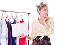 Женщина pin-вверх держа пустое примечание над вешалкой и платьями Стоковая Фотография