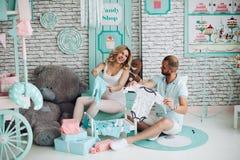 Женщина Pragnant и ее симпатичные показывая младенцы один другого одежд Стоковые Фотографии RF