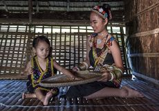Женщина Rangus племенная в ее традиционном племенном костюме работая в ее доме в Kudat, Малайзии Стоковые Изображения