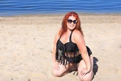 Женщина Redhead в солнечных очках отдыхая на пляже Стоковые Изображения RF