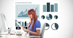 Женщина Redhead держа документ на столе компьютера против диаграмм Стоковое фото RF