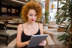 Женщина Redhead используя планшет в ресторане Стоковые Изображения RF