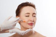 Женщина 40s среднего возраста получая поднимаясь впрыску botox в губах доктором изолированным на белой предпосылке Макрос Космети стоковое фото rf