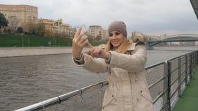 Женщина Selfie на Smartphone стоя на обваловке реки и видов на город стоковое фото rf