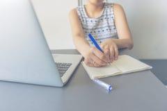 Женщина Sian сидя на таблице делая назначения в библиотеке колледжа стоковые фото