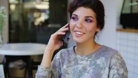 Женщина Smartphone говоря на телефоне пока сидящ в кафе Она усмедется Красивая молодая женщина имея вскользь сток-видео