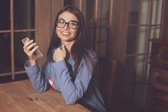 Женщина Smilling на таблице Стоковые Изображения