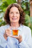 Женщина Smilng зрелая выпивая травяной чай Стоковое Изображение