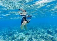 Женщина snorkeling в морской воде мелководного моря Шноркель показывает лицевой щиток гермошлема большого пальца руки полностью Стоковые Фото