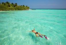 Женщина snorkeling в ясных тропических водах перед экзотическим isl Стоковая Фотография
