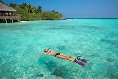 Женщина snorkeling в ясных тропических водах перед экзотическим isl Стоковые Изображения