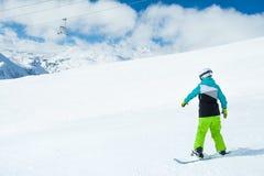 Женщина Snowboarder на ландшафте предпосылки снежных высоких гор Стоковые Изображения RF