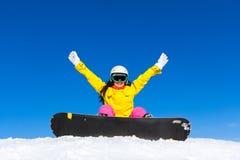 Женщина Snowboarder сидя на наклоне горы снега Стоковые Изображения