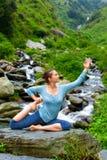 Женщина Sorty подходящая делая asana йоги outdoors на тропическом водопаде Стоковое Фото