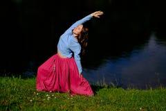 Женщина Sporty пригонки кавказская делая позицию представления ратника Virabhadrasana 2 asana в природе Стоковые Фотографии RF
