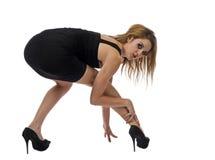 Женщина squating вниз и смотря назад Стоковая Фотография