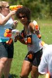 Женщина Squirts люди в драке пушки воды группы стоковые изображения rf