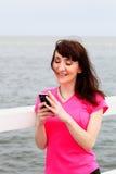 Женщина texting на ее мобильном телефоне Стоковые Изображения