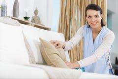 Женщина tidying вверх по софе стоковая фотография